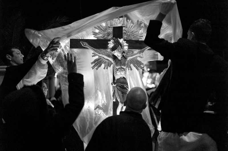 Rain. Altar boys drape the cross of Jesus Christ with plastic