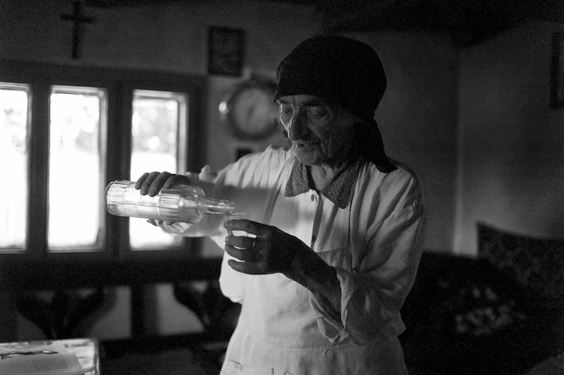 A women pours a traditional Romanian fruit brandy called Pálinka