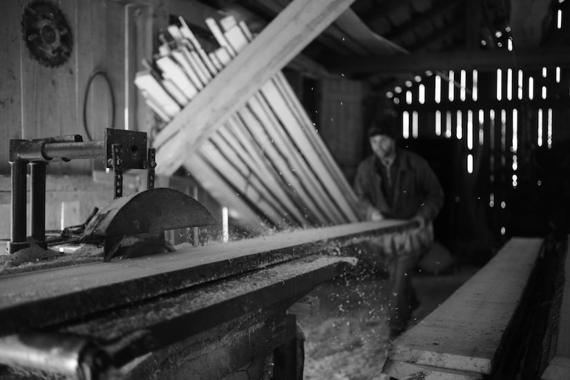 A worker saws lumber by hand in a sawmill